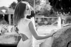 美丽的年轻微笑的妇女黑白画象在喷泉附近的 库存照片