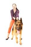 美丽的年轻快乐的妇女在主角德国牧羊犬举行 免版税库存照片