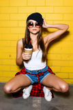 美丽的年轻性感的女孩饮料咖啡和坐在太阳镜的黄色墙壁背景,红色格子花呢上衣,短裤附近 图库摄影