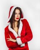 美丽的年轻愉快的妇女在圣诞老人穿衣在圣诞节背景 在微笑的白人妇女的背景 秀丽查出的纵向白色 库存照片