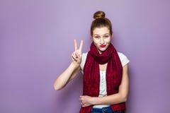 美丽的年轻愉快的微笑的妇女画象,显示两个手指或胜利姿态,穿戴了白色T恤杉和红色围巾在pu 免版税库存图片