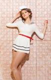 美丽的画报女孩打扮了摆在桃红色背景墙壁上的水手 免版税图库摄影