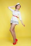 美丽的画报女孩打扮了摆在黄色背景墙壁上的水手 图库摄影