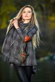 美丽的年轻摆在秋天的时装模特儿佩带的外套和绑腿停放 免版税库存图片