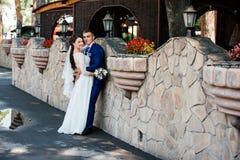 美丽的年轻新娘和新郎在石墙附近在公园 库存照片