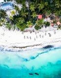 美丽的绿松石海洋遇见有房子和棕榈的非洲海岛 免版税图库摄影