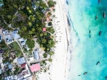 美丽的绿松石海洋遇见有房子和棕榈的非洲海岛 免版税库存图片