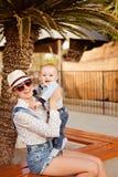 美丽的年轻母亲举行sm的帽子、太阳镜和短裤 库存图片