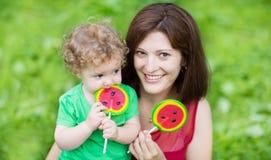美丽的年轻母亲和她的吃糖果的小女儿 免版税库存照片