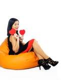 美丽的年轻浅黑肤色的男人坐有红色华伦泰hea的长沙发 库存图片