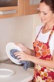 美丽的年轻浅黑肤色的男人洗涤的盘。 图库摄影