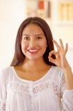 美丽的年轻深色的妇女佩带的白色女衬衫上面,面对互动的照相机做完善的圈子使用手指 免版税库存图片