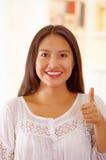 美丽的年轻深色的妇女佩带的白色女衬衫上面,面对互动的照相机给赞许微笑,明亮 免版税库存照片