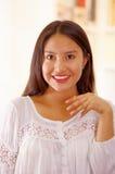 美丽的年轻深色的妇女佩带的白色女衬衫上面,面对微笑的照相机,明亮的家庭背景 免版税库存图片