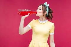 美丽的从瓶的少妇站立的和饮用的汁液 免版税库存照片