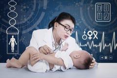 美丽的医生核对婴孩 库存照片