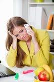 美丽的年轻疲乏的妇女谈话在电话 免版税库存照片