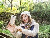 美丽的年轻白种人妇女在秋天拍selfie照片 免版税库存图片