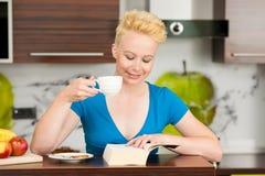 美丽的年轻白种人白肤金发的在ki的妇女饮用的咖啡 免版税图库摄影