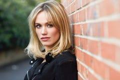 美丽的年轻白肤金发的妇女在都市背景中 免版税图库摄影