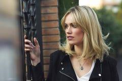 美丽的年轻白肤金发的妇女在都市背景中 库存图片