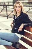 美丽的年轻白肤金发的妇女在都市背景中 免版税库存照片