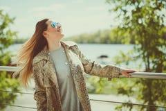 美丽的年轻白肤金发的妇女室外在湖岸,是周道,温暖的过滤器是应用的,在您的头发的风 免版税库存照片
