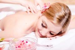 美丽的年轻白肤金发的妇女愉快微笑在温泉按摩治疗期间 库存图片