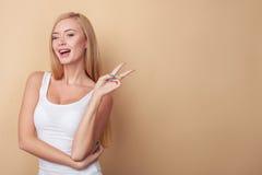 美丽的年轻白肤金发的妇女打手势 免版税库存图片