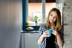 美丽的年轻白肤金发的妇女饮用的咖啡 免版税库存图片