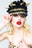 美丽的年轻白肤金发的妇女画象侈奢的帽子的在白色背景 免版税库存照片