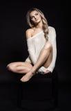 美丽的年轻白肤金发的妇女画象坐黑桌 库存图片