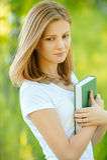 美丽的年轻白肤金发的妇女画象有书的 图库摄影