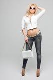美丽的年轻白肤金发的妇女画象有卷发的 女孩穿一件白革夹克,蓝色牛仔裤和 免版税库存照片