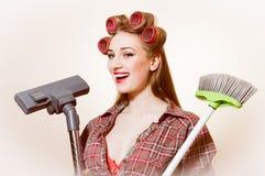 美丽的年轻白肤金发的看在白色拷贝空间背景的照相机的妇女拿着吸尘器的和刷子 免版税库存图片