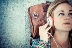 美丽的年轻白肤金发的行家妇女听的音乐 免版税库存照片