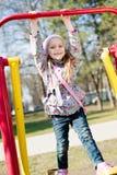 美丽的滑稽的逗人喜爱的小女孩获得乘坐摇摆的乐趣看照相机&愉快微笑在公园在春天或秋天 图库摄影