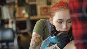 美丽的年轻红发在她的女孩客户的腿的妇女纹身花刺艺术家刺字的图片特写镜头在演播室户内 股票录像