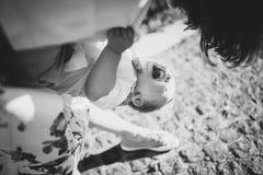 美丽的黑色纵向白人妇女 美丽的年轻妈妈和快乐的可爱的白肤金发的男孩使用,获得乐趣 妇女爱她的儿子 免版税库存照片