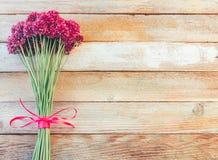 美丽的紫色葱属花花束栓与在木减速火箭的背景的一条紫色丝带与文本的空间 图库摄影
