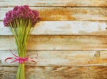 美丽的紫色葱属花花束栓与在木减速火箭的背景的一条紫色丝带与文本的空间 免版税图库摄影