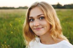 美丽的年轻蓝眼睛的女孩画象有有轻的头发的迷人的微笑和笑涡在她的调查照相机的面孔stan 图库摄影