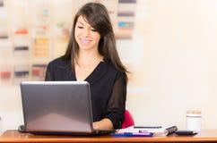美丽的年轻深色的女孩与膝上型计算机一起使用 免版税库存照片