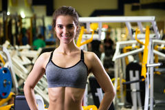 美丽的年轻运动的妇女 健身在体育俱乐部的女孩训练用锻炼设备 免版税库存照片
