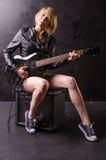 美丽的年轻金发碧眼的女人在有电吉他的黑皮夹克穿戴了在黑背景 免版税库存照片