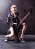 美丽的年轻金发碧眼的女人在有电吉他的黑皮夹克穿戴了在黑背景 免版税图库摄影