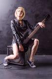 美丽的年轻金发碧眼的女人在有电吉他的黑皮夹克穿戴了在黑背景 免版税库存图片