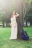 美丽的boho女孩画象在树附近的与蓝色吉他 免版税库存照片