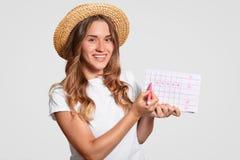 美丽的Cuacasian妇女演播室照片有迷人的微笑,穿草帽,穿戴在T恤杉,举行期间日历,标记w 图库摄影