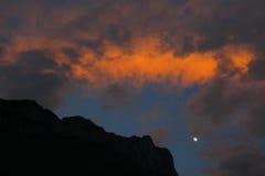 美丽的Gemu圣洁山和月亮在火焰状晚霞,云南,中国山顶的剪影  免版税库存图片